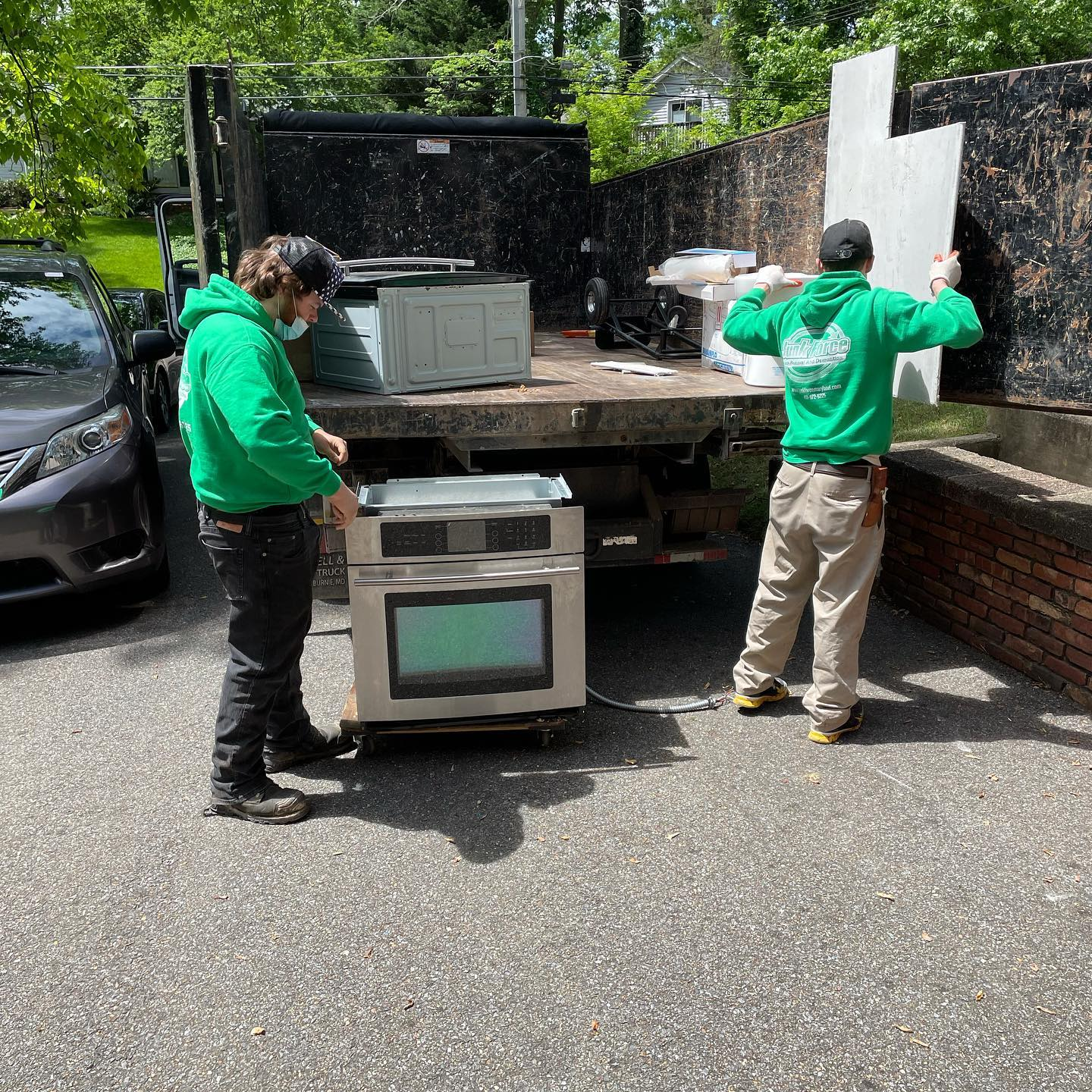 The Junk Force team loads appliances into its Junk Removal truck